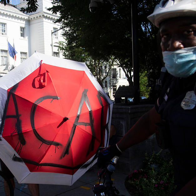 "A marcher opens their umbrella, spray painted with ACAB, in the face of Metro Police Department bike officer K.E. Brown as the march passes through Sheridan Circle Park on their way to Georgetown on Saturday, August 8. ACAB stands for ""All Cops are Bastards."" It's a frequent chant at their protests and others."
