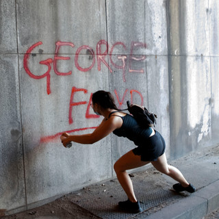 """A protester spray paints """"George Floyd"""" on an interstate underpass on Saturday, May 30, 2020, the first full day of protests in Washington, D.C. after Floyd's death in Minneapolis, MN. Floyd was killed when Minneapolis police officer Derrick Chauvin kneeled on Floyd's neck for nine minutes and twenty-nine seconds while he was handcuffed on the ground."""
