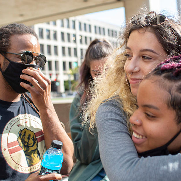 Cass carries Bella Raymond-Paez to a makeshift dance floor during jail support outside the U.S. Courthouse on October 5, 2020. Jail support is always carried out the day after a comrade is arrested. People wait outside with food, coffee, shoelaces and more.