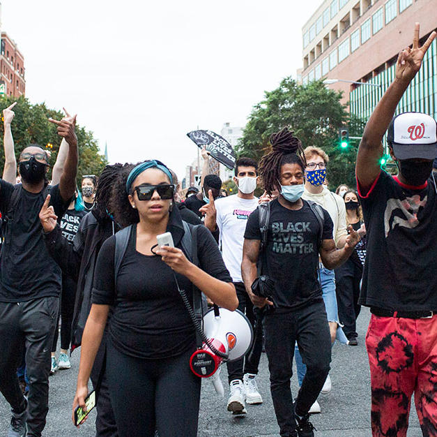 Brittney Henderson-Fiestas, center, and Drew Boddie, right, lead D.C. Protests' march on Saturday, September 26.