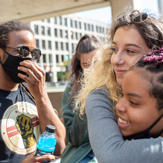 Cass carries Bella to a makeshift dance floor during jail support outside the U.S. Courthouse on October 5. Jail support is always carried out the day after a comrade is arrested. People wait outside with food, coffee, shoelaces and more.