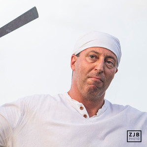 Jeremy Sellers, serving as the Laplas dagniea, or sword-bearing master of ceremonies, open Sunday's service on Bayou St. John on June, 23, 2019. Voodoo practicioners dance, sing and bring offerings to the gods on the banks of Bayou St. John on St. John's Eve, the day before the Feast of St. John, a Catholic holiday. This photograph was made for the Mid City Messenger.