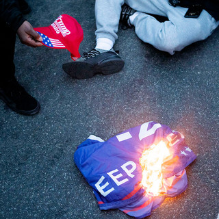 "Counter-protesters in the ""Fuck MAGA"" march burn Trump memorabilia after the Million MAGA March on Saturday, November 14. The event brought roughly 10,000 Trump supporters, as well as Neo-fascists, to Washington, D.C. to challenge the outcome of the 2020 election, which made Joe Biden president-elect. President Trump has not accepted the outcome and has yet to concede as of November 18."