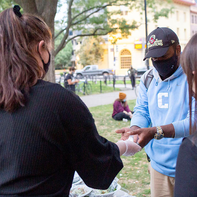 Volunteers sanitize peoples' hands before serving meals at DuPont Circle on Saturday, October 10. The organization stepped up to serve food for the unhoused population at DuPont Circle when the They/Them Collective, who usually does this, was not able after being raided by U.S. Park Police.