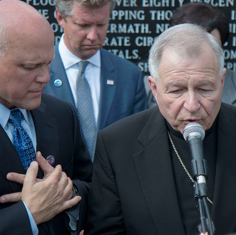 New Orleans mayor Mitch Landrieu, left, bows his head as Archbishop Gregory Aymond, right, leads a prayer at a Katrina 10 event.