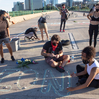 Brittney Henderson-Fiestas, bottom right, lays out candles for a memorial to Deon Kay on the Francis Scott Key Bridge on Saturday, September 5. Kay, 18, was shot in the back and killed by D.C. Metropolitan Police Department officer Alexander Alvarez in Southeast D.C. that week.
