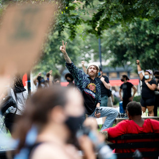 A man playing chess throws up the peace sign in solidarity as D.C. Protests passes DuPont Circle during a march on. Saturday, August 15.