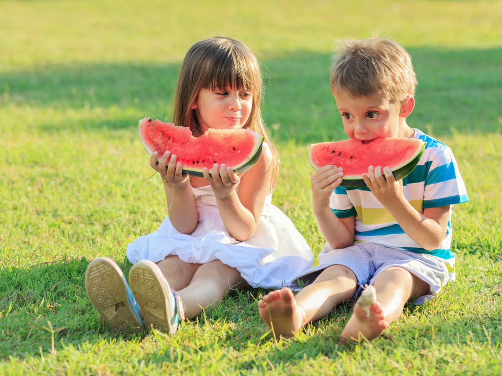 Little girl and a boy eating watermelon