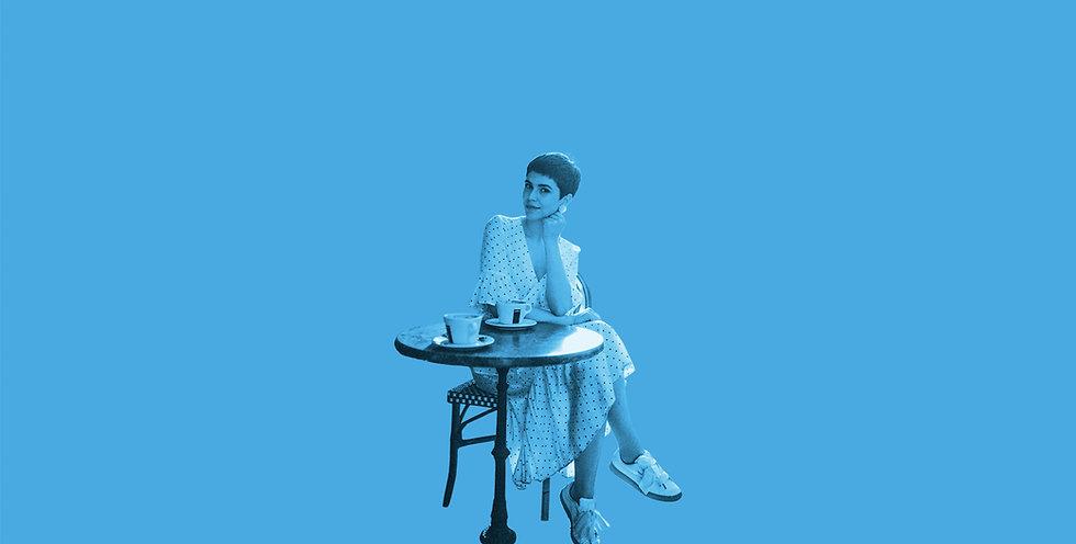 Mulher sentada numa mesa de um café ou restaurante a ouvir a música ambiente.