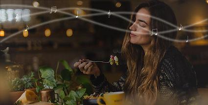Mulher comendo num restaurante, saboreando a comida e a música do ambiente com os olhos fechados. Representa a experiência do cliente num ambiente ideal. Notas musicais também aparecem na imagem.