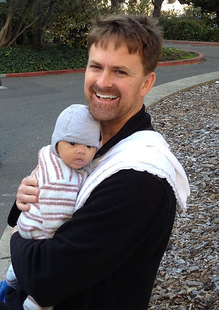 Photo of Scott Wallin laughing and holding his infant daughter, who is also looking at the camera