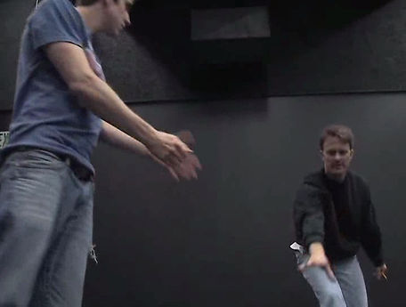 A photo of Scott Wallin directing a play in a black box theatre. He is caught in mid-motion reaching forwarding, gesturing to one of his actors.