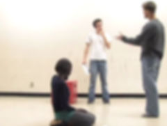 Scott Wallin speaks to a student, who listens, holding a script in one hand and brings his finger up to his chin. Another student kneels on the floor in the forground.