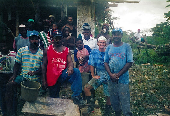 Seventeen Jamaican men, ranging in age from a young adolescent to a senior, as well as a white male in his mid-20s, pose in front of a partially completed concrete structure. Their clothes are soiled from the hard labor. Each man is either grinning or looking serious. In the background a woman, wearing a headscarf, sits on a toppled tree and looks at the camera.