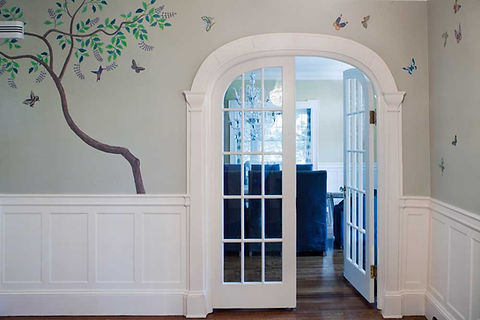 decorative wall painting of trees, birds and butterflies around a french door