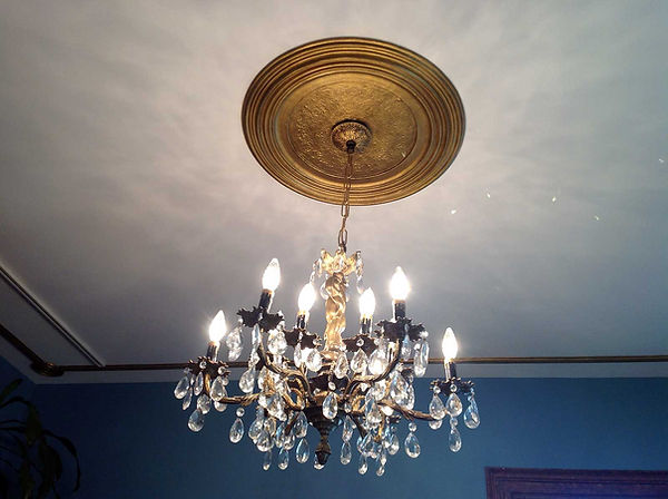 Chandelier hanging from a restored gold painted plaster ceiling medallion