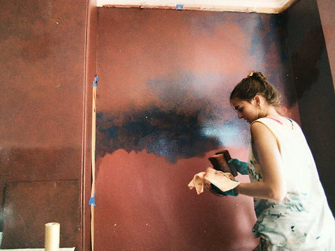 The artist applying a leather look effect on a wall with orange and blue glazes