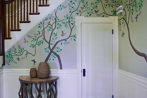 trees with birds and butterflies painted on a wall below a stairwell with an end table designed to look like tree branches