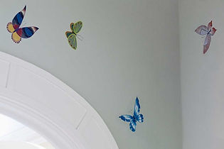 Butterflies painted on a pale green wall over a door arch