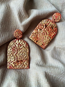 Large orange and gold statement earrings on a beige fabric background.