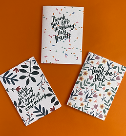 Three cards on an orage background. The top centre card has a confetti design and says 'Thanks for washing my pants'. The left card has a botanical print and says 'Sorry for what i said when we were teching'. the right card has a floral print and says 'Don't be shit'.
