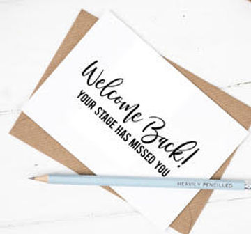 White card with black text reading 'Welcombe Back! Your stage has missed you'. The card is on a brown envelope, on a white wooden background. On top of the card is a light blue pencil.