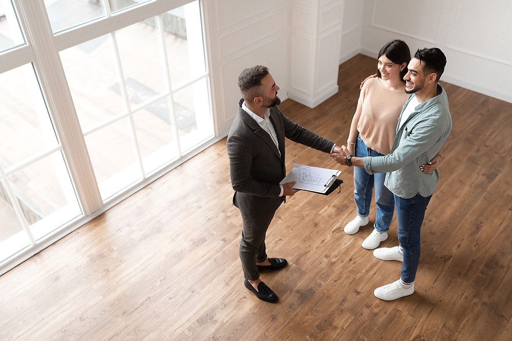 property manager shaking hands with tenants who came to see the property