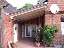 Vordach weiß grundiert zwischen zwei Häusern als Pultdach