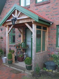 Vordach mit grüner Blende aus Holz mit Sonne