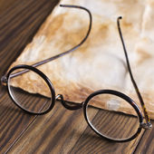 depositphotos_34654043-Old-glasses-on-the-vintage-document