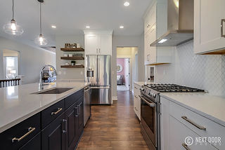 white kitchen cabinets with navy island and floating shelves