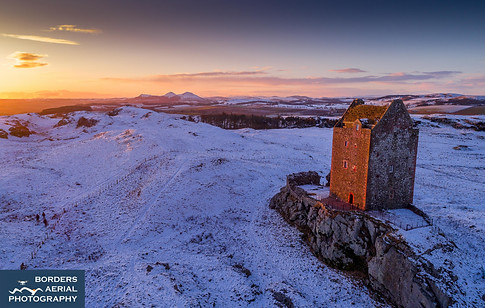 Aerial sunset at Smailholm Tower in the snow, Scottish Borders
