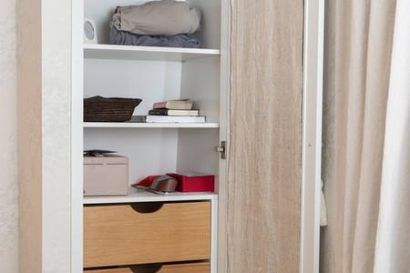 Innvendig i garderobeskapet ser vi en kombinasjon av hyller og delikate treskuffer i eik