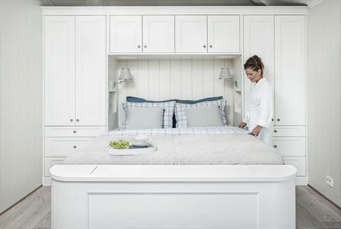 Spesialtilpasset garderobeløsning med skuffer, skap og med innebygget dobbelt seng i lys grå farge