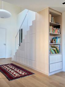 Bokhylle og garderobe i slett finert stil bygget inn i trapperom