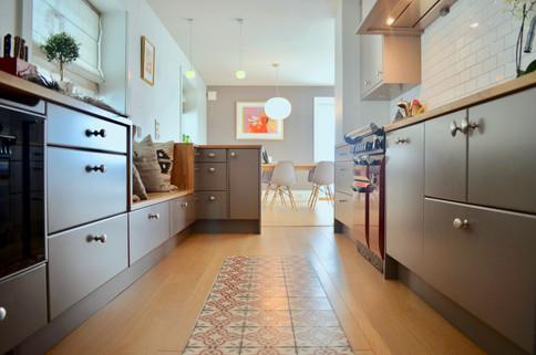 Rødfargen i falcon komfyren og flisene blir en fin kontrast mot den duse grå kjøkkeninnredningen og det varme gulvet i eik. Sømløse overganger i benkeplaten som følgere ned over sittebenken