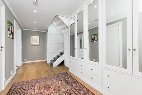 Store speilflater på garderobedørene gir en økt romfølelse samtidig som rammedørene ivaretar et eksklusivt preg