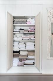 Garderobeskap til håndklær og sengetøy inffelt i nisje. Her med glassdør og gardiner bak. Lyse behaglige farger