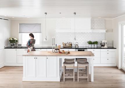 Kjøkkeninnredning med profilerte fronter møbel sokkel spesial designet kjøkkenhette. Benkeplater i mørk granitt og massiv eik