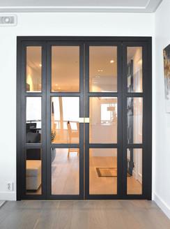 Dørene markerer et innbydende stemningsskifte mellom det hvite dagslyset i stuen og det varme lyset i yttergangen