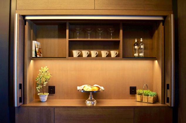 Bak de elegante foldedørene openbarer det seg en egen kjøkkenavdeling i seg selv med benk til for eksempel anretning