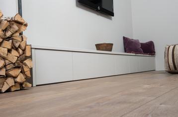 Bred tv benk med slette fronter helt til gulv gir et minimalistisk uttrykk i denne tv stuen