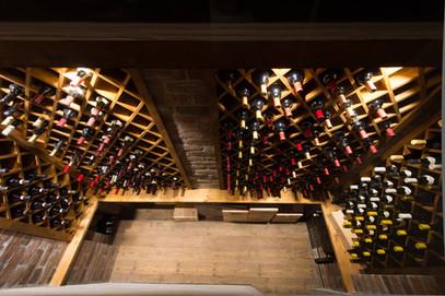 Plassbygget vinrom med vinhyller i kryss og  åpne hyller til vinkasser i beiset furu utførelse