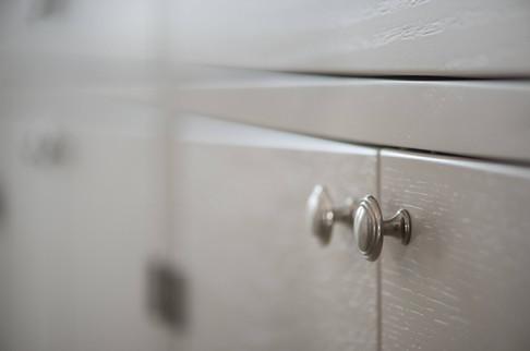 Detalj fra kjøkken med malt treverk i lys grå og knotter i tinn