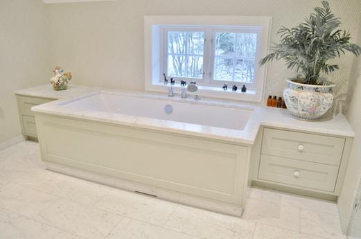 Innebygget badekar med møbelfronter og skuffer på sidene