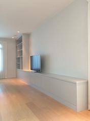Minimalistisk lav og bred TV benk med slette fronter samt påmontert bokhylle
