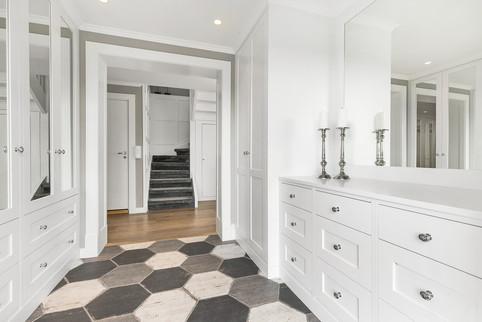 Garderobeskap til tak og plasstilpasset kommode med speil i ramme gir et variert og luftig uttrykk