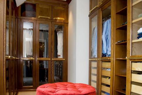 Eksklusiv walk in closet i mørkbeiset eik med glassdører for innsyn og stilfulle håndtak i messing. Sittepuff i rødt gir et artig fargeinnslag