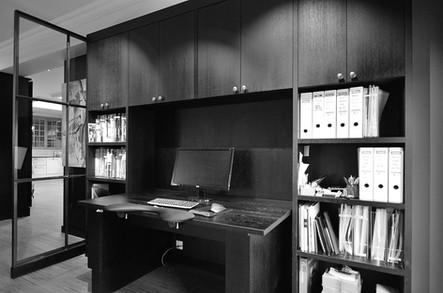 Et lite kontormiljø med hev og senk bord. Arkivskap med dører i topp og åpne hyller på sidene. Dempet sort farge og antikk tinn knotter