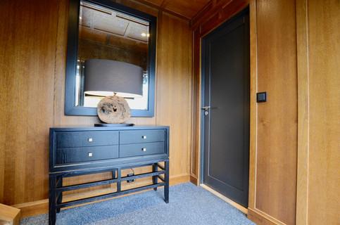 Konsollbord i sortmalt eikefinér designet av Gustavian AS. Bronsjespeil med ramme i sort. Vegger og tak i antikk eik